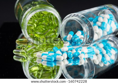 Natural supplements and vitamins on black background - stock photo