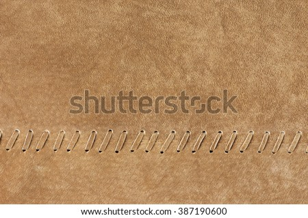 Natural tan color suede texture with decorative stitch as background. - stock photo