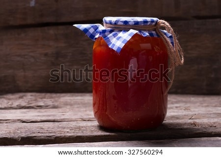 Natural tomato juice on old wooden boards. Ecoproduct on wooden shelf. Canning juice in the cellar. - stock photo