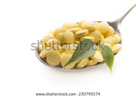Natural vitamin supplements on the  spoon, isolated on the white. - stock photo