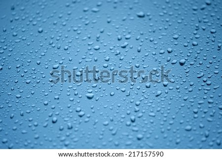 Natural water drops on glass in blue - stock photo