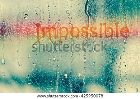 """natural water drops on glass window with the text """"Impossible"""" - stock photo"""