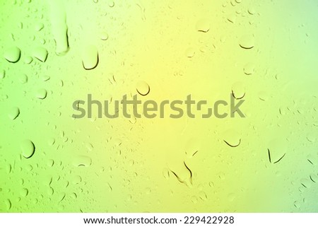 Natural water drops on green window glass background - stock photo