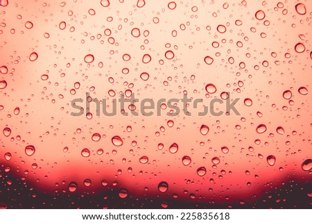 Natural water drops on red window glass background - stock photo
