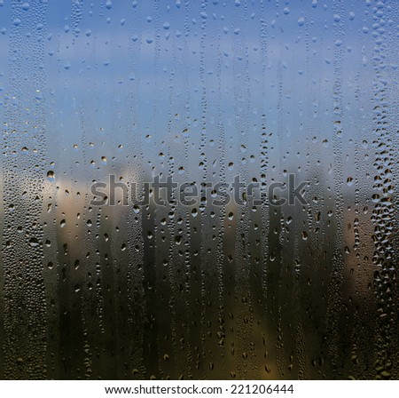 Natural water drops on window glass with nature background - stock photo