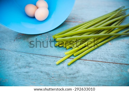 Natural white eggs in a blue bowl and Spring onions over old blue wooden table. - stock photo