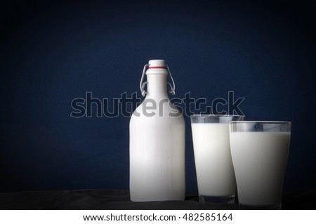 Natural whole milk in a jug and a glass isolated on a dark background closeup.