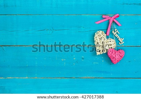 Natural wicker heart with pink polka dot ribbon, rope heart and Family hanging on antique rustic teal blue wood background - stock photo