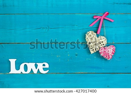 Natural wicker heart with pink polka dot ribbon, rope heart and Love hanging on antique rustic teal blue wood background - stock photo