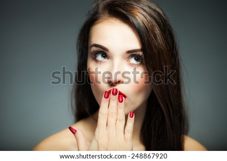 Natural woman face with red nails and lips on dark background - stock photo