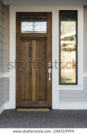 Natural Wood Front Door with Panels and Windows - stock photo
