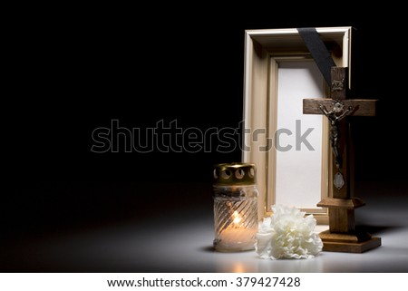 natural wooden mourning frame with crucifix, flower and candle on dark background - stock photo