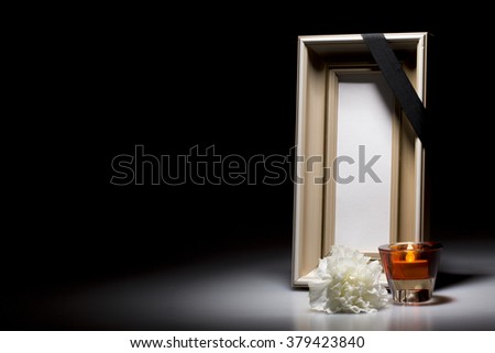 natural wooden mourning frame with flower and candle on dark background - stock photo