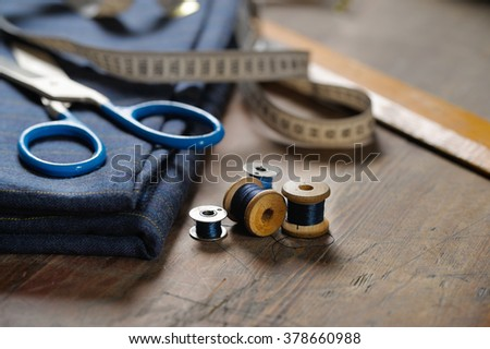 Natural wool, sewing machine bobbin, scissors on a wooden table - stock photo