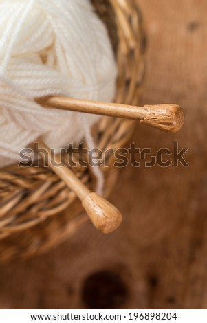 Natural woolen yarn and knitting on vintage wooden background.