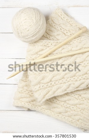 Natural woolen yarn and knitting with wood needles on white wooden background. Top view point. - stock photo