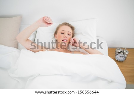 Natural yawning blonde lying in bed with closed eyes in bright bedroom