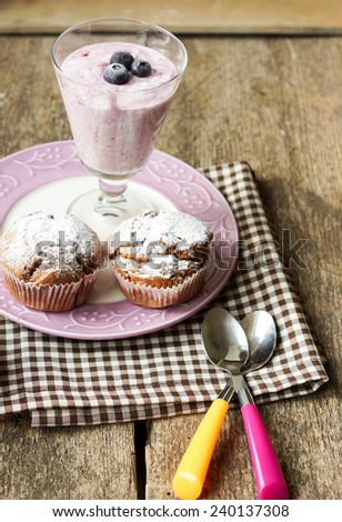 Natural yoghurt with fresh blackcurrants and muffins - stock photo