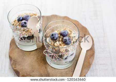 Natural yogurt with fresh blueberries and home made muesli cereals , selective focus - stock photo
