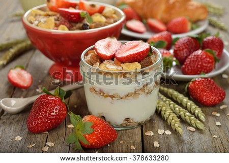 Natural yogurt with granola and strawberries on a wooden background - stock photo