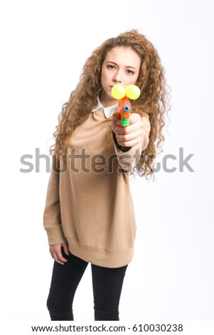 Natural young girl on white background with water gun