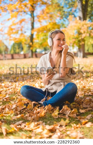 Natural young woman listening to music on headphones as she sits amongst the fallen autumn leaves in a park looking to the side with a happy smile - stock photo