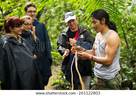 NATURALIST LOCAL GUIDE WITH GROUP OF TOURIST IN CUYABENO WILDLIFE RESERVE, ECUADOR