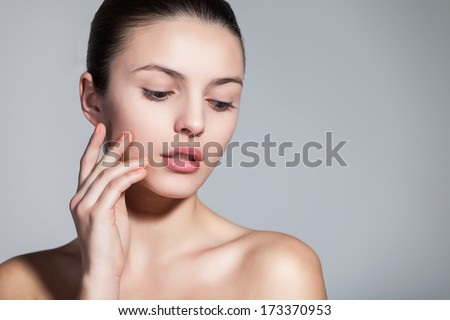 Naturally beautiful brunette woman with flawless skin touching her face dreamily over gray background