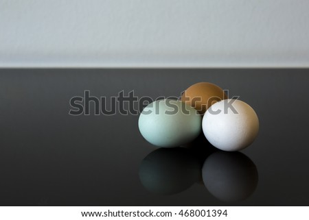 Naturally colored white, green, and brown eggs on a ceramic plate