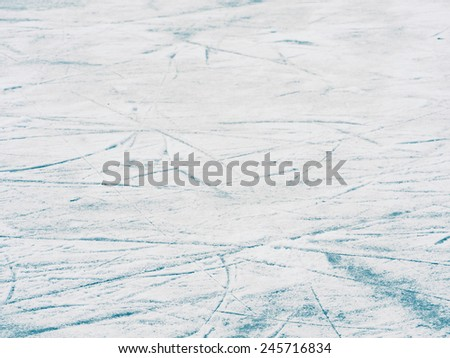 Naturally frozen hockey ice rink surface texture with skates trails, abstract background of blue ice and white snow, selective focus  - stock photo