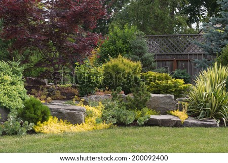 Naturally sculptured flat top rocks from northwest Oregon are placed in a beautifully landscaped backyard among a variety of perennial evergreens and shrubs.  - stock photo