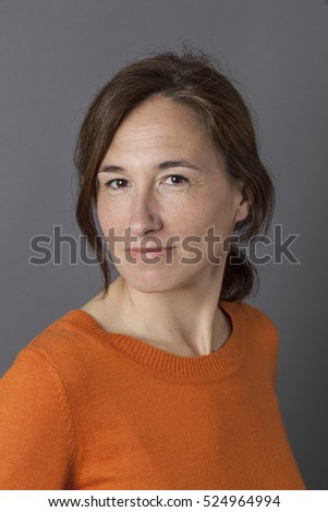 naturally sexy middle aged woman posing with an orange sweater, relaxing and smiling for wellness over grey background, indoors