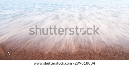 Nature abstract water on beach in motion washes like mist over sand leaving patterns - stock photo