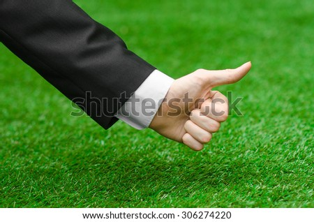 Nature and business topic: the hand of man in a black suit showing a thumbs up gesture against a background of green grass