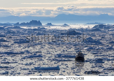 Nature and landscapes of Greenland. Travel on the scientific vessel among ices. Studying of a phenomenon of global warming. Ices and icebergs of unusual forms and colors. Midnight - stock photo