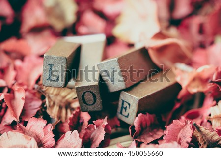 Nature background or wallpaper:  wood stamp with love letters on colorful leaves on the ground full frame shot. - stock photo