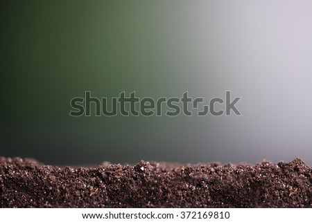 Nature background, pile of soil against green defocused grass with copy space - stock photo