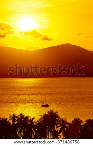 Nature Background. Scenic View Landscape Of Tropical Island Coast At Orange Sunset Over Beautiful Sea With Floating Boat And Palms Silhouette. Scenery. Travel To Thailand. Tourism. Summer Vacations  - stock photo