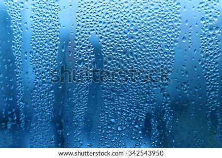 Nature blue background with water drops on glass - stock photo