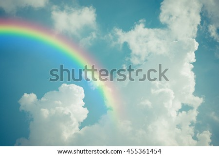 Nature cloudscape with blue sky and white cloud with rainbow , processed in vintage style - stock photo