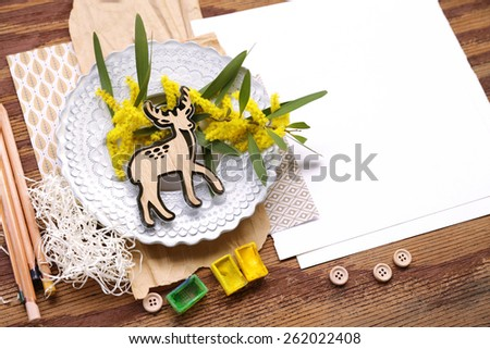 Nature composition with baby deer placed over yellow flowers in rounded white plate over shredded paper, pencils and watercolors with white placeholder paper on the right on top of brown vintage wood - stock photo