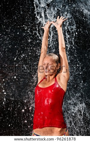 Nature concept - Young and emotional girl in red tank-top enjoying jungle waterfall - stock photo