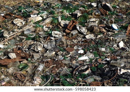 Nature contaminated by glass metal plastic waste Discarded household garbage on the meadow Environmental pollution and ecology problem concept. Human health hazard concept.