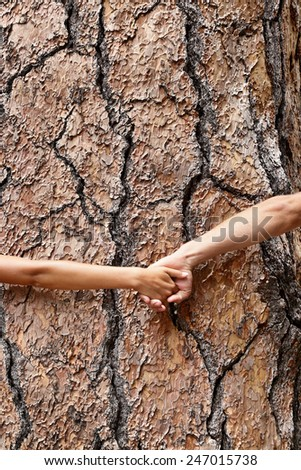 Nature Earth lovers - tree huggers holding hands around bark embracing Mother nature. Eco friendly concept showing environment conservation issues. - stock photo