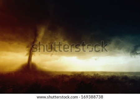 Nature force background - dark stormy sky, huge tornado hits small town  - stock photo