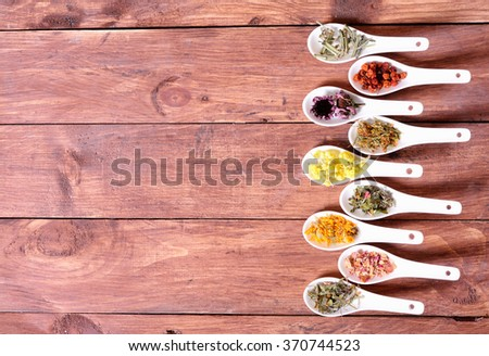 Nature medicine . Herbs in ceramic bowls on wooden background .