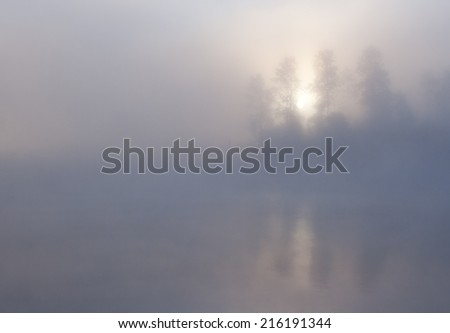 Nature morning sunrise summer scene: forest and trees visible through fog (mist) over the water surface (river, lake, pond) with a blur pattern of waves and reflections. Can be used as a wallpaper. - stock photo