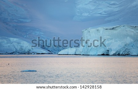 Nature of Antarctic Peninsula. Early morning in the Antarctic fjords. Glaciers and icebergs. Travel on deep pure waters among ices of Antarctica. Fantastic snow landscapes. - stock photo