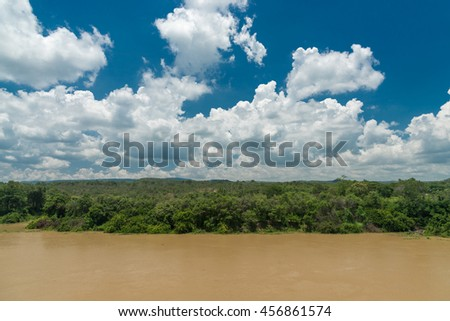 nature of clouds , blue sky , forest and river in a clear day