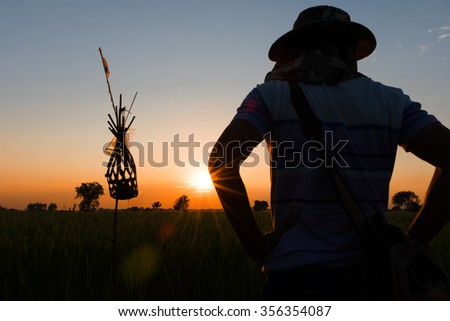 nature of countryside at sunset light; with men standing back light